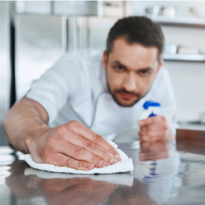 Worker Cleaning Kitchen Surface