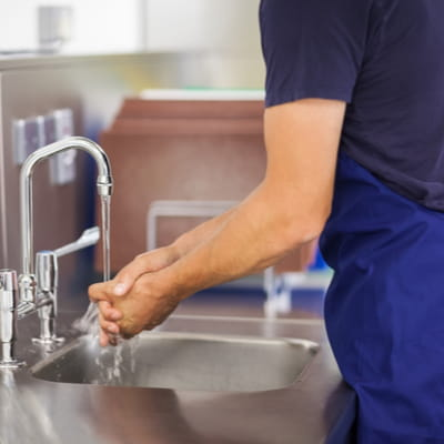 Kitchen porter washing hands