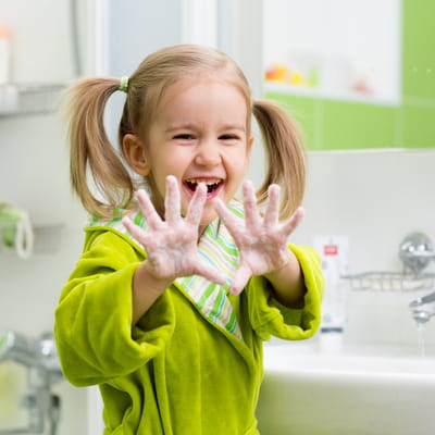 Little girl having fun washing her hands