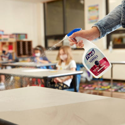 Teacher spraying PURELL Surface Spray in classroom with children present