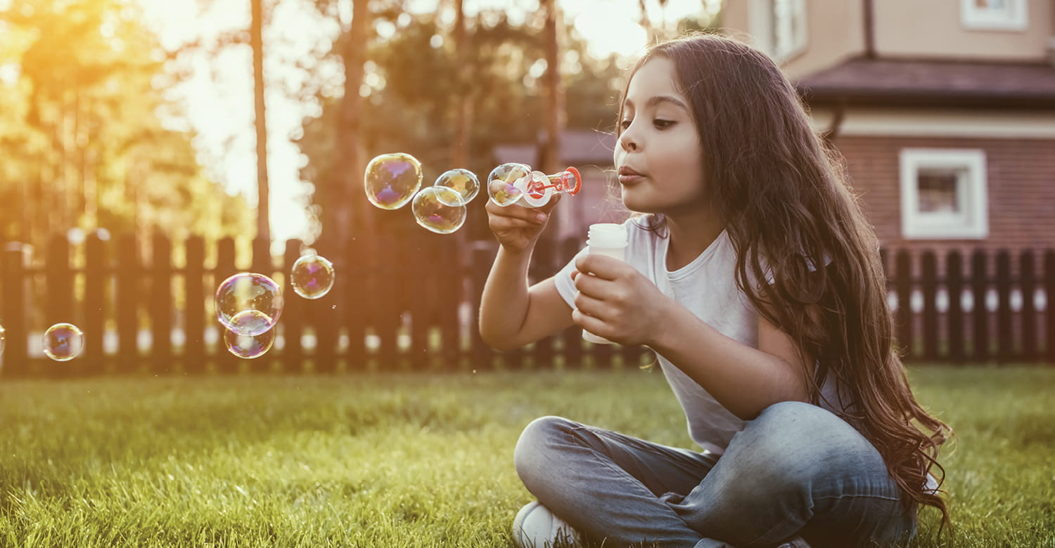 Girl blowing bubbles in her yard