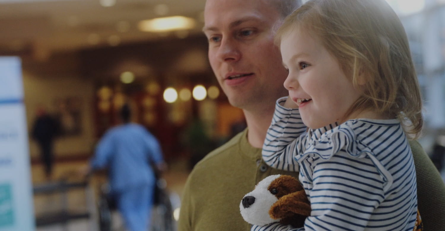 Smiling Dad carrying small daughter through a hospital lobby