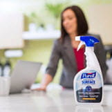 Woman wiping down table with PURELL Surface